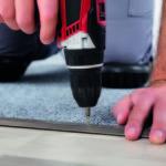 man drilling carpet fitting